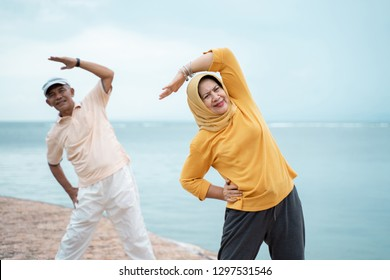 senior couple asian muslim stretching and exercising together at beach