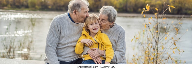 Senior couple with baby grandson in the autumn park. Great-grandmother, great-grandfather and great-grandson BANNER, LONG FORMAT