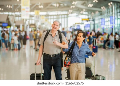 Senior couple with bags at airport.