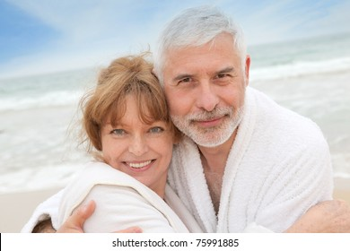 Senior couple at the beach with spa bathrobe