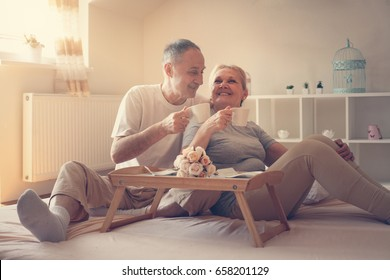 Senior couple in bed. Senior people drinking coffee in bed.