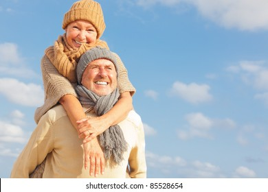 senior couple with blue sky in background having fun in autumn season on the coast in vacation