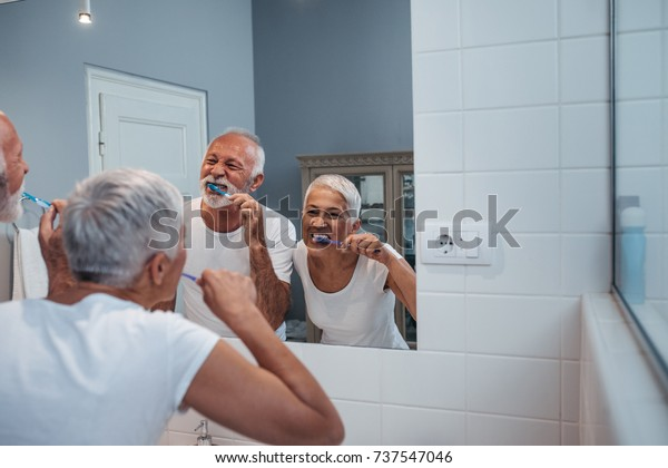 A senior couple brushing their teeth in a brightly lit living bathroom in the morning.