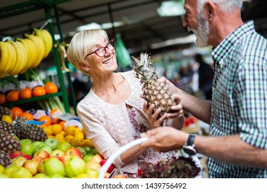 Senior couple buying fresh vegetables and fruits at the local market