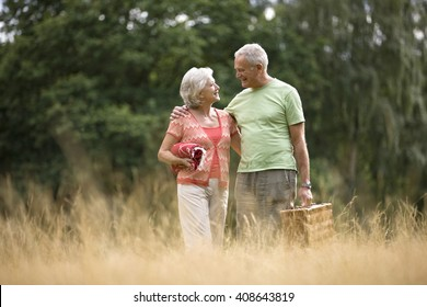 A senior couple carrying a blanket and a picnic basket