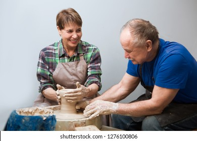 Senior couple in casual clothes and aprons making ceramic pot on pottery wheel in workshop. hobby on pension