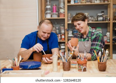 Senior couple in casual clothes and aprons at pottery workshop painting pottery. hobby on pension