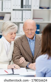 Senior couple chatting to a business broker in an office as they receive financial planning advice for their retirement