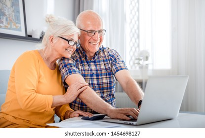 Senior couple checking bills using laptop at home