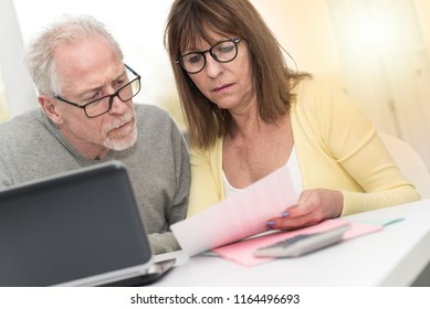 Senior couple checking financial document at home, light effect