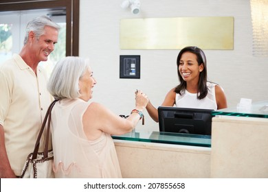 Senior Couple Checking In At Hotel Reception
