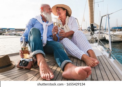 Senior couple cheering with champagne on sailboat during summer vacation - Mature people having fun drinking and laughing together - Joyful elderly lifestyle, travel and love concept - Focus on faces