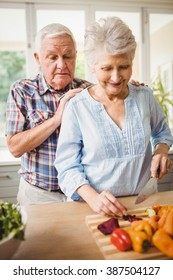 Senior couple chopping vegetables in kitchen