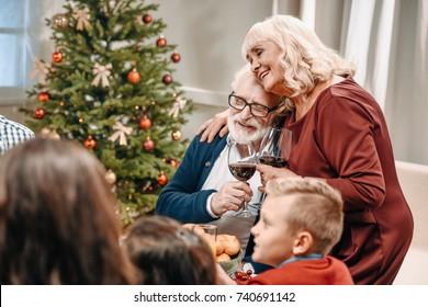 senior couple clinking glasses while celebrating christmas with family