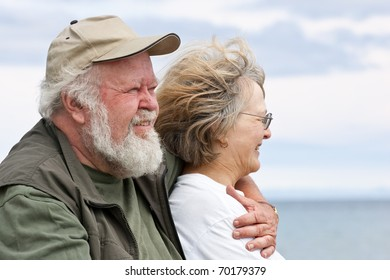 A senior couple, close together, looking out at the water, with water and sky behind.