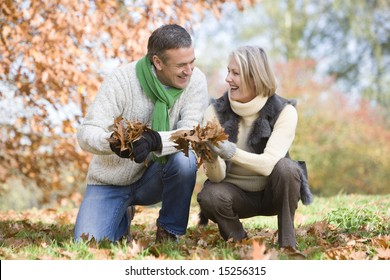 Senior couple collecting autumn leaves together