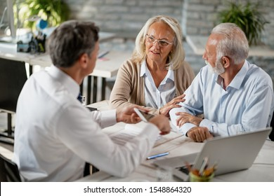 Senior couple communicating with insurance agent while having consultations with him in the office. Focus is on woman.