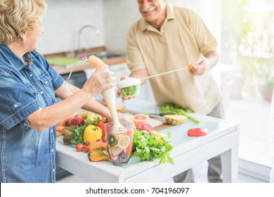 Senior couple cooking healthy vegan meal with fruits and vegetables together - Old happy people taking care about diet - Vegetarian and healthy lifestyle concept - Focus on woman hand - Warm filter