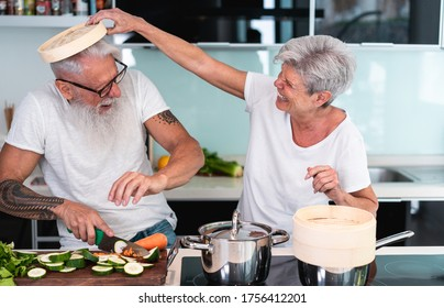 Senior couple cooking at home while preparing vegetarian lunch - Mature people cutting vegetables for healthy meal inside house kitchen - Joyful elderly lifestyle and food concept - Focus on woman eye