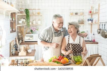 Senior couple is cooking in the kitchen and smiling while cooking together in kitchen .