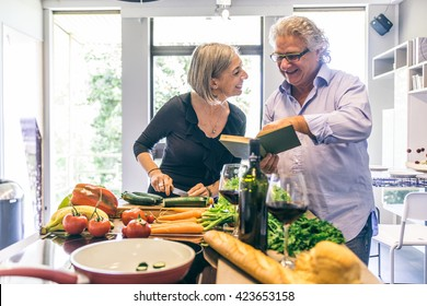 Senior couple cooking meal at home, man reading a cooking recipe book and woman cutting vegetables - Happy mature couple in the kitchen
