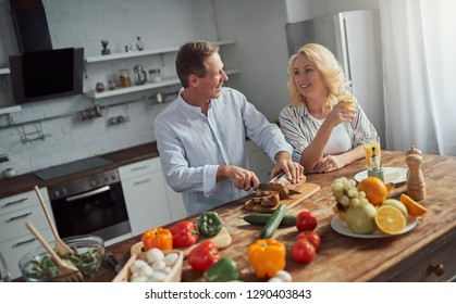 Senior couple is cooking on kitchen. Beautiful woman and handsome man are spending time together at home. Healty lifestyle concept.