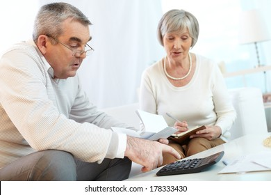 Senior couple counting their expenses