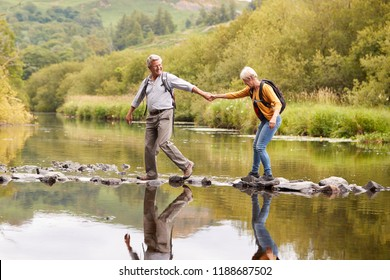 Senior Couple Crossing River Whilst Hiking In UK Lake District