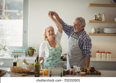 Senior couple dancing in kitchen at home