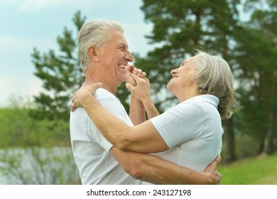 Senior couple dancing near lake