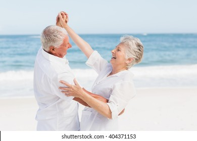 Senior couple dancing on the beach on a sunny day