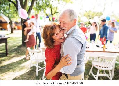 A senior couple dancing on a garden party outside in the backyard.