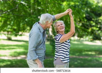 Senior couple dancing in park