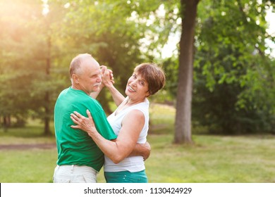 Senior couple dancing in park on sunny day
