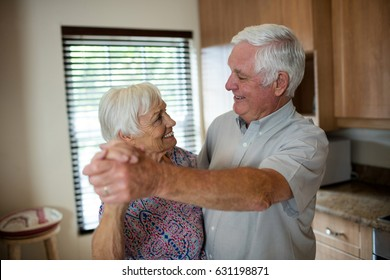 Senior couple dancing together in kitchen at home