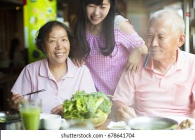 Senior Couple and daughter Enjoying hot pots In Restaurant
