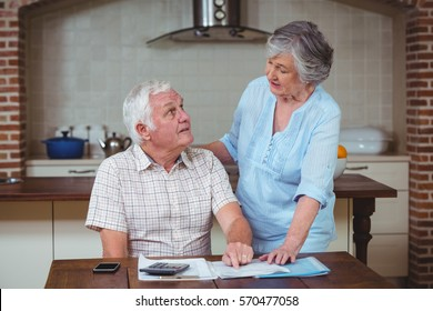 Senior couple discussing with bills at home