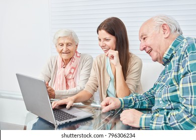 Senior couple is doing a computer course and looking curiously at the laptop PC