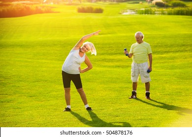 Senior couple doing exercises. Woman and man outdoor. Health of joints and muscles. Fitness changed our life.