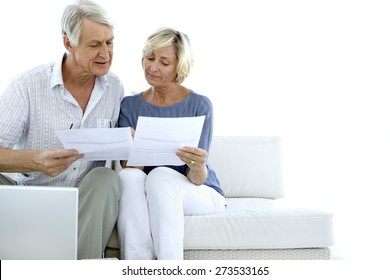 Senior couple doing home finances. White background with copy space.