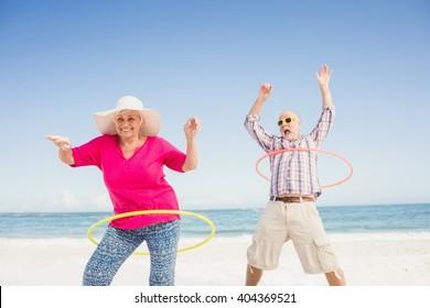 Senior couple doing hula hoop on the beach