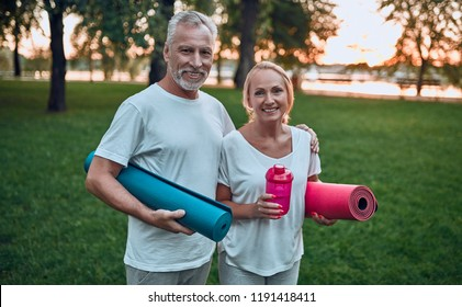 Senior couple is doing sport outdoors. Standing with yoga carpet and shaker in hands in park during sunrise.