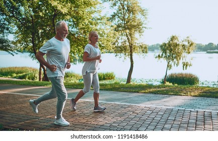 Senior couple is doing sport outdoors. Running in park in the morning.