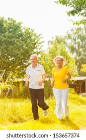 Senior Couple doing sport outdoors, jogging on a road or path in the nature