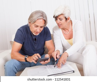 Senior couple doing their finances with the woman checking the accounts while the husband adds up the figures on the calculator