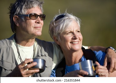 Senior couple drinking coffee from travel cups outdoors