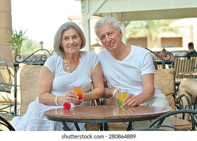 Senior couple drinking juice outside at the resort during vacation