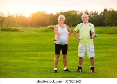 Senior couple with dumbbells. People smiling and doing exercise. Sport is in our blood. Strengthen joints and muscles.