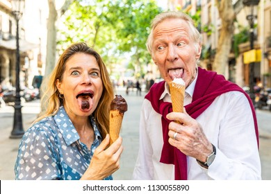 Senior couple eating ice cream and having fun in Barcelona. Adult woman and man making funny faces and grimacing while enjoying a fresh ice cream on a hot summer day in Spain. Summer and food concepts