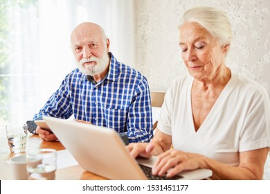 Senior couple at e-learning together at laptop computer at home